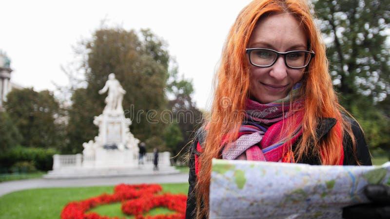 De vrouwentoerist van Yong met rood haar en glazen die kaart in Burggarten, Wenen, Oostenrijk kijken royalty-vrije stock afbeelding