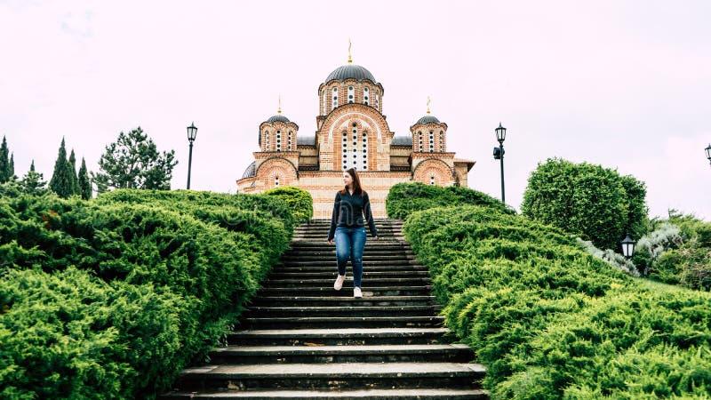 De vrouwentribune van de roodharige jonge volwassen heks op trap tegen orthodoxe rode baksteen oude kerk met kruis de mooie toeva stock foto's