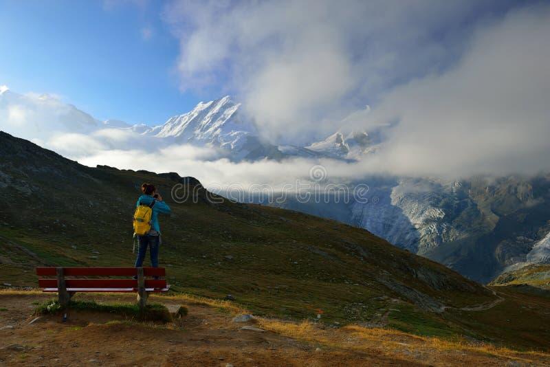 De vrouwenwandelaar kijkt van Rotenboden-post aan berg stock foto's
