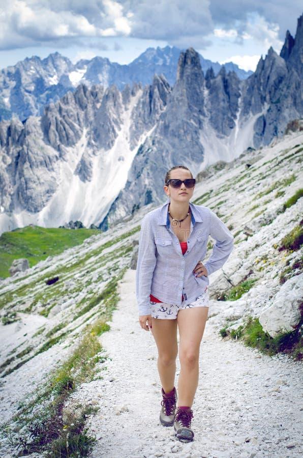 De vrouwenwandelaar ligt heeft een rust op bergen Pieken zoals een achtergrond Zonnige dag trekking Abstracte verlichtingsachterg stock fotografie