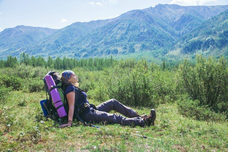 De vrouwenwandelaar met rugzakzitting op groen gras en het gevoel ontspannen met gesloten ogen bij achtergrond van hooggebergte royalty-vrije stock afbeeldingen