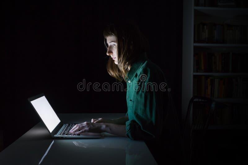De vrouwenwerken bij laptop computer laat in de avond stock afbeeldingen