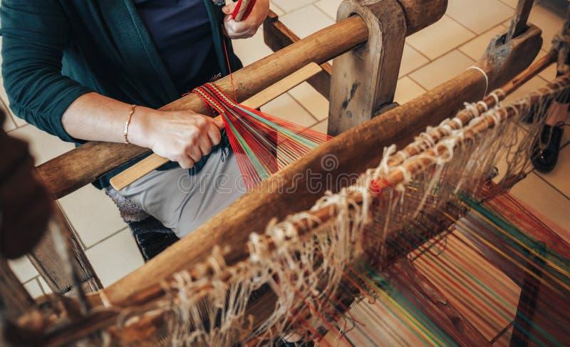 De vrouwenwerken bij oud wevend weefgetouw Het traditionele Russische houten hand-wevend weefgetouw voor maakt doek stock afbeelding