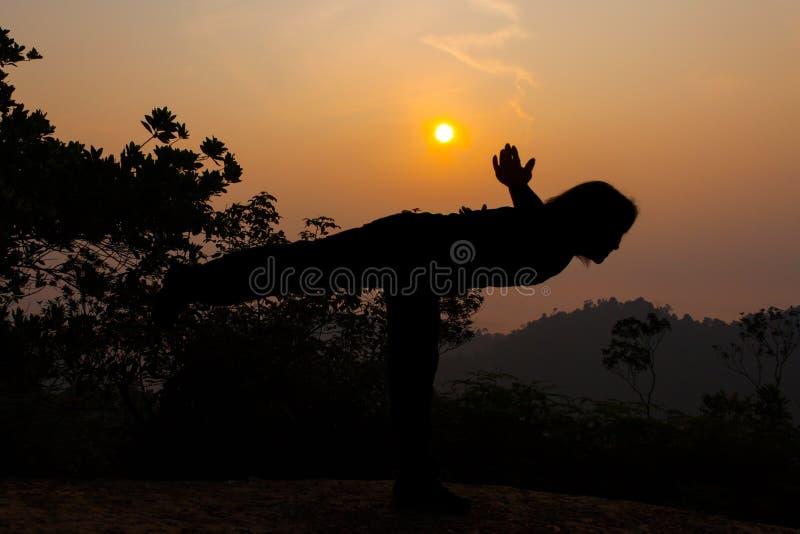 De vrouwenyoga stelt in silhouet op heuveltop tijdens zonsopgang royalty-vrije stock fotografie