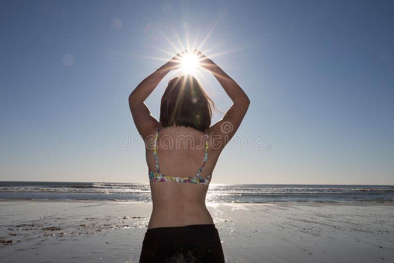 De vrouwenyoga van het silhouetmeisje op het strand bij zonsondergangzon in handen stock fotografie