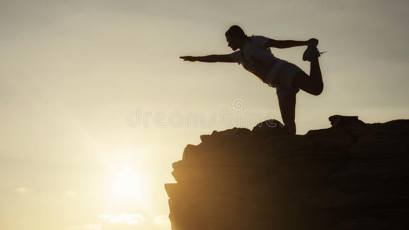 De vrouwenyoga van de silhouetsport bij heuveltop stock afbeeldingen