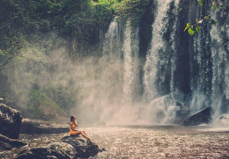 De vrouwenzitting dichtbij waterval die van de zon, Phnom Koulen in Siem genieten oogst, Kambodja royalty-vrije stock afbeeldingen