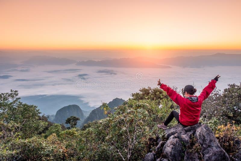 De vrouwenzitting en heft omhoog handen op heuvel met mist in zonsopgang bij wildreservaat op royalty-vrije stock afbeeldingen