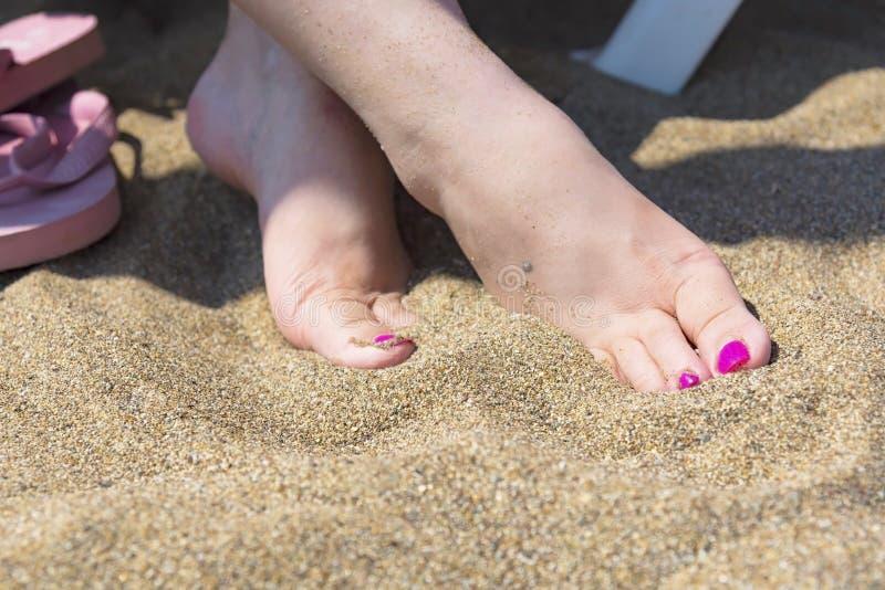 De vrouwenzitting op de naakte voeten van een zitkamerstoel op een zand, sluit omhoog stock afbeelding