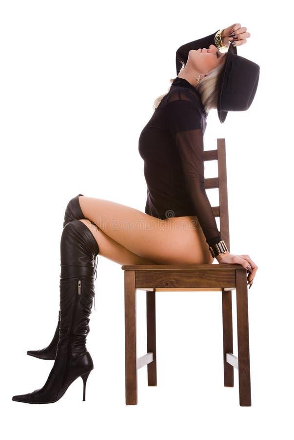 De vrouwenzitting van de blonde op stoel stock foto