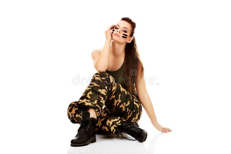 De vrouwenzitting van de Ypung mooie militair op de vloer stock afbeeldingen