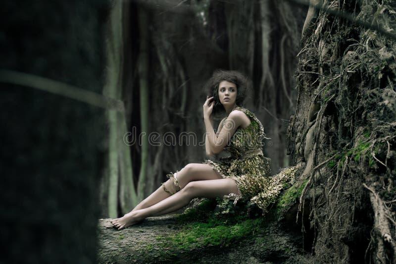 De vrouwenzitting van Eco op de boomstam royalty-vrije stock foto