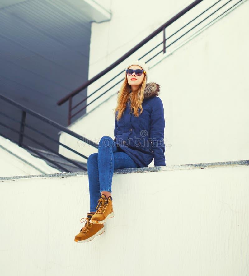 De vrouwenzitting van het manier mooie blonde in de winterstad over witte muur stock foto's