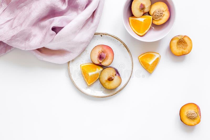De vrouwenzomer breackfast met sinaasappel en perzikvruchten en de stof op witte vlakte als achtergrond leggen model royalty-vrije stock foto