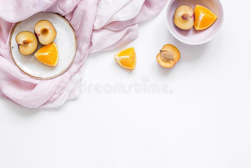De vrouwenzomer breackfast met sinaasappel en perzikvruchten en de stof op witte vlakte als achtergrond leggen model stock fotografie