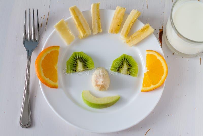 De vruchten en de groenten schikten een beroep doend te kijken op jonge geitjes in grappig gezicht stock afbeeldingen
