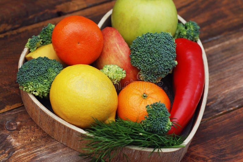 De vruchten en de Groenten in Hart vormden Houten Doos Broccoli, appelen, Peper, mandarijn over Houten Achtergrond banner Natuurl stock afbeelding