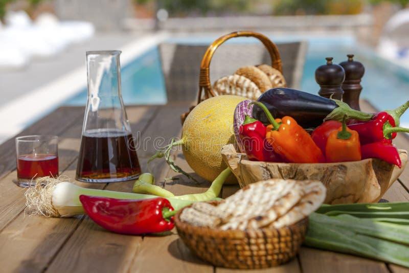 De vruchten, de groenten, de wijn en het brood op de lijst in de zomer tuinieren royalty-vrije stock afbeeldingen