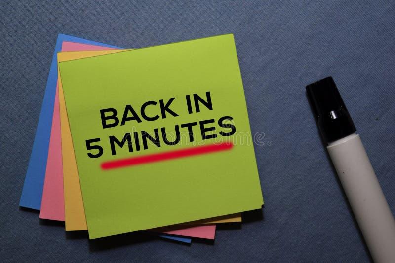 De vuelta en 5 minutos en notas adhesivas aisladas en Office Desk foto de archivo libre de regalías