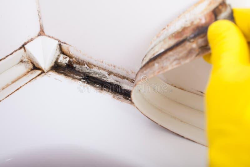 De vuile die tegels in een badkamers overgieten met dichtingsproduct in vorm en schimmel wordt behandeld royalty-vrije stock foto