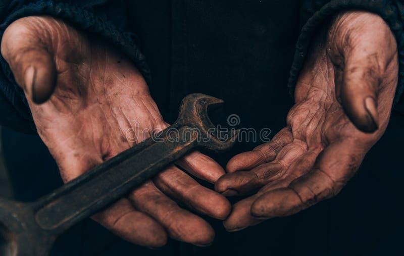 De vuile handen van een mens, een werkende mens, een mens voerden zijn handen af terwijl het werken, een slechte mens stock foto
