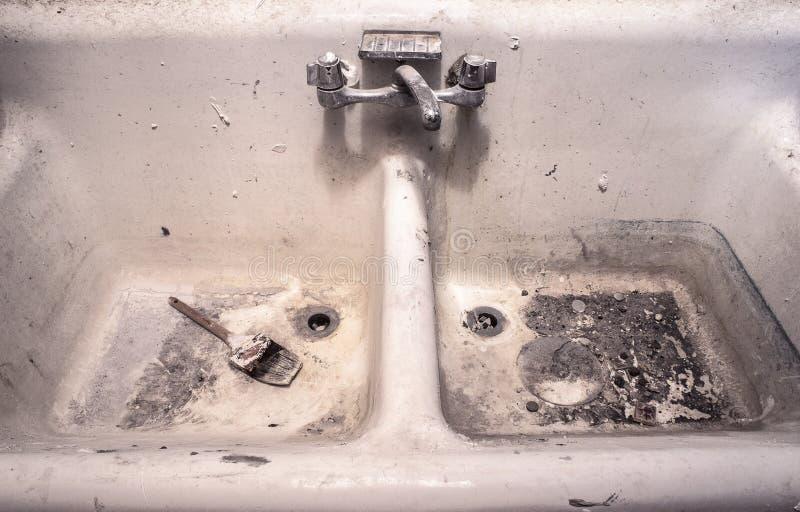 De vuile oude witte gootsteen van het porseleinwerk met de droge zitting van de verfborstel in slordige crud stock foto