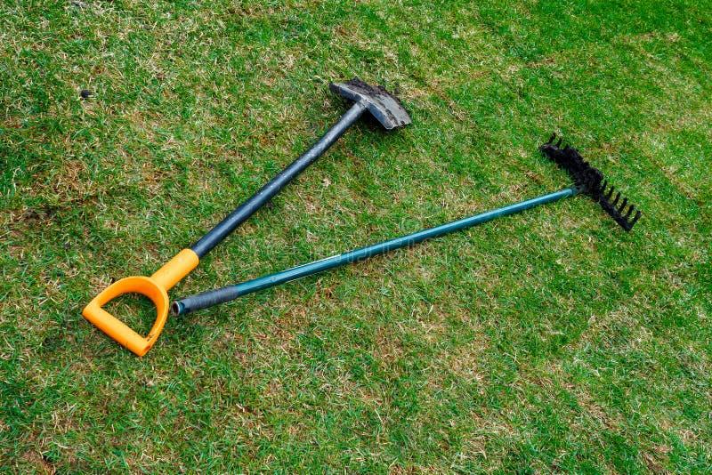 De vuile schop en de harken van de tuinman liggen op het verse gerolde gazon stock foto's