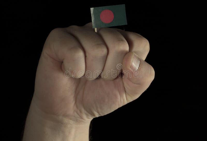 De vuist van de mensenhand met Inwoner van Bangladesh vlag die op zwarte wordt geïsoleerd royalty-vrije stock afbeelding