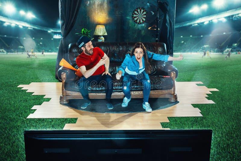 De vurige fans zitten op de bank en het letten op TV in het midden van een voetbalgebied royalty-vrije stock foto's