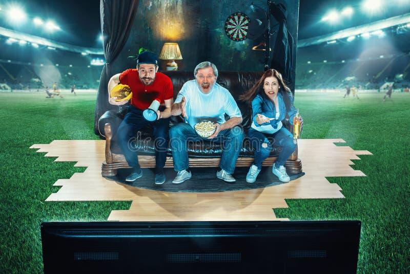 De vurige fans zitten op de bank en het letten op TV in het midden van een voetbalgebied stock afbeelding