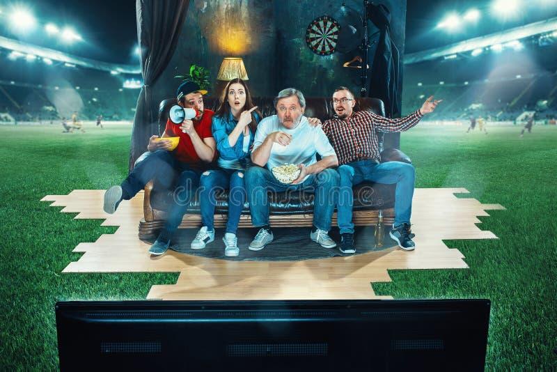 De vurige fans zitten op de bank en het letten op TV in het midden van een voetbalgebied stock foto's