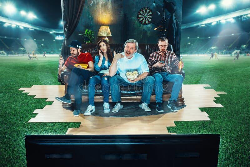 De vurige fans zitten op de bank en het letten op TV in het midden van een voetbalgebied stock foto