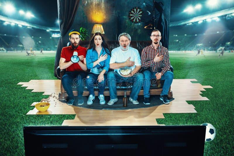 De vurige fans zitten op de bank en het letten op TV in het midden van een voetbalgebied royalty-vrije stock afbeelding