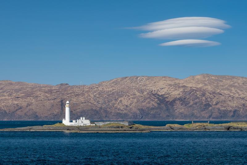 De vuurtoren van Eileanmusdile in Schotland, met hooglandlandschap op de achtergrond stock afbeelding