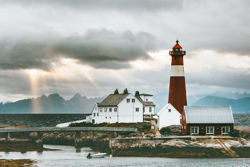 De Vuurtoren van het Landschapstranoy van Noorwegen bij zonsondergangoverzees en bergen op achtergrondreis royalty-vrije stock afbeeldingen