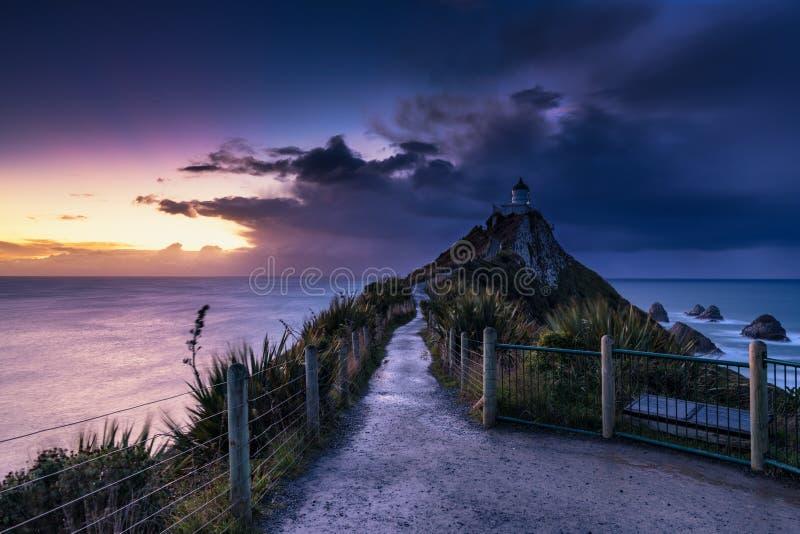 De vuurtorenzonsopgang van het goudklompjepunt, Nieuw Zeeland stock fotografie
