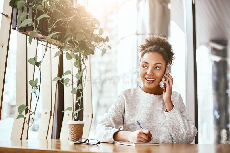 De waarde van een idee ligt in het gebruiken van het Aantrekkelijke bedrijfsvrouw die bij bureau in modern bureau werken stock fotografie