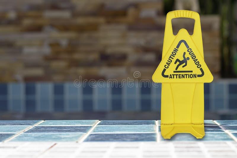 De waarschuwing plateert natte die vloer naast de pool van geel plastiek wordt gemaakt stock fotografie
