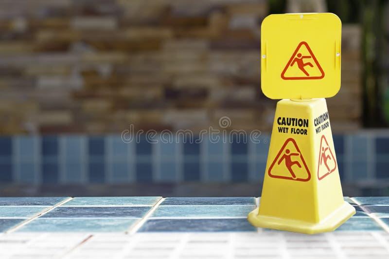 De waarschuwing plateert natte die vloer naast de pool van geel plastiek wordt gemaakt royalty-vrije stock foto