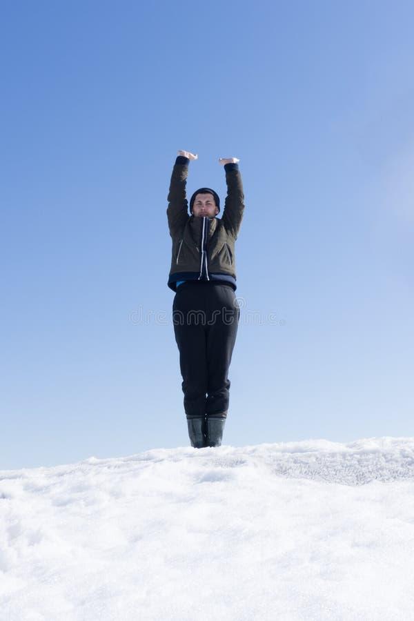 De wandelaar bij de bovenkant van een rots met rugzak geniet van zonnige dag stock afbeeldingen