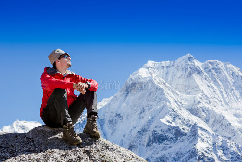 De wandelaar bij de bovenkant van een rots geniet van zonnige dag royalty-vrije stock foto's