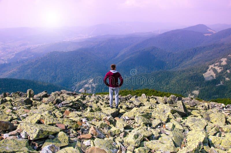 De wandelaar bij de bovenkant van een rots met rugzak geniet van zonnige dag royalty-vrije stock foto's