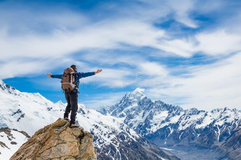 De wandelaar bij de bovenkant van een rots met zijn opgeheven handen geniet van zonnige dag stock afbeeldingen