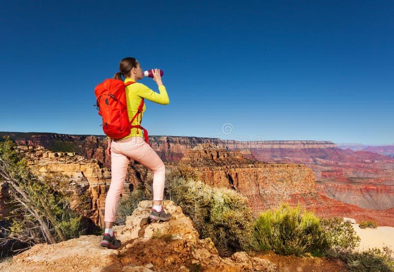 De wandelaar drinkt watertribune op rand van Grote canion royalty-vrije stock foto