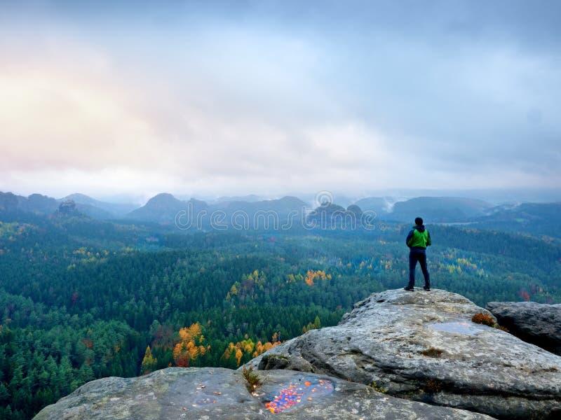 De wandelaar in groene windcheater, GLB en de donkere trekkingsbroeken bevinden zich op berg piekrots stock foto