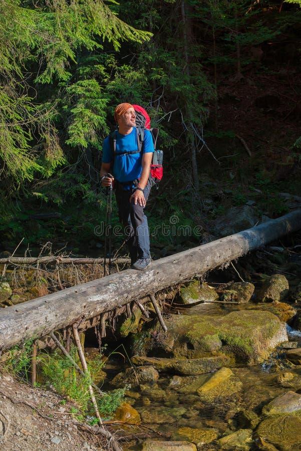 De wandelaar kruist bergrivier door een voorlopige brug royalty-vrije stock foto's