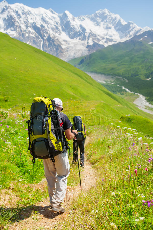 De wandelaar neemt een rust tijdens wandeling in de bergen van de Kaukasus, Georgië royalty-vrije stock fotografie