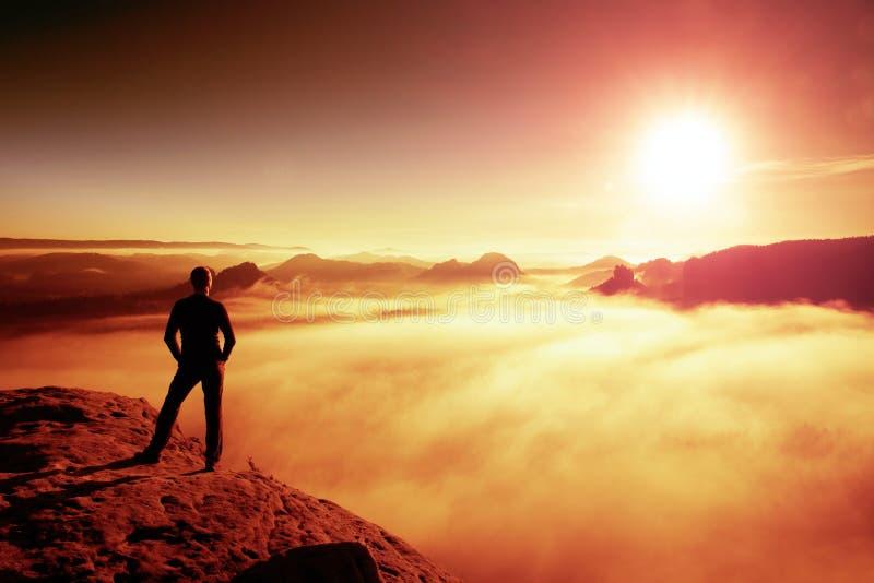 De wandelaar in zwarte bevindt zich op rots abve vallei binnen dageraad en horloge aan Zon Mooi ogenblik het mirakel van aard stock afbeelding