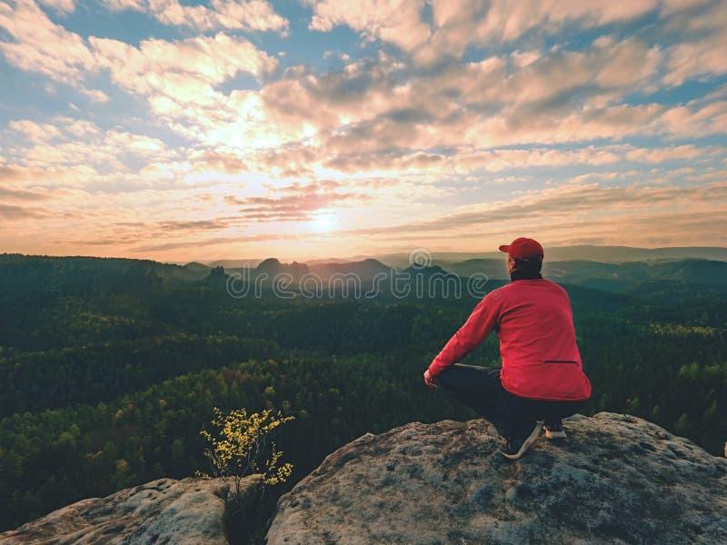 De wandelaarmens neemt een rust op bergpiek De mens legt op top, stock foto