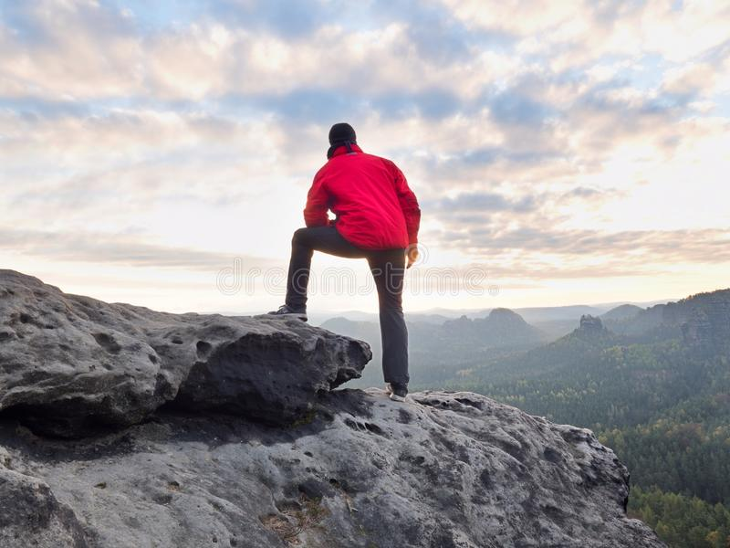 De wandelaarmens neemt een rust op bergpiek De mens legt op top, de vallei van de blaasbalgherfst royalty-vrije stock foto's
